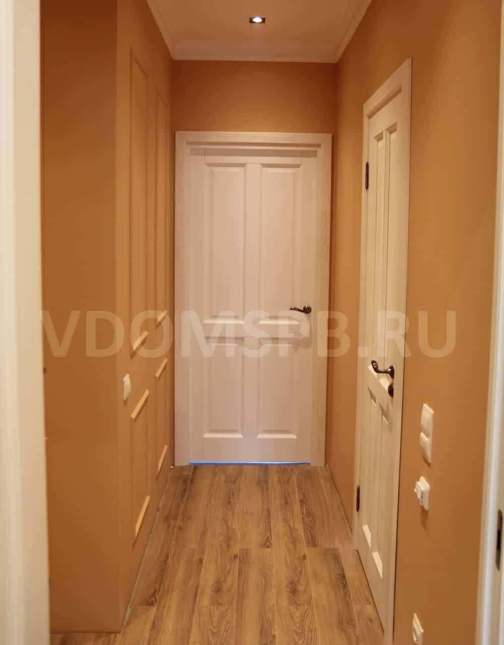 Белые двери и крашенные стены с рамками