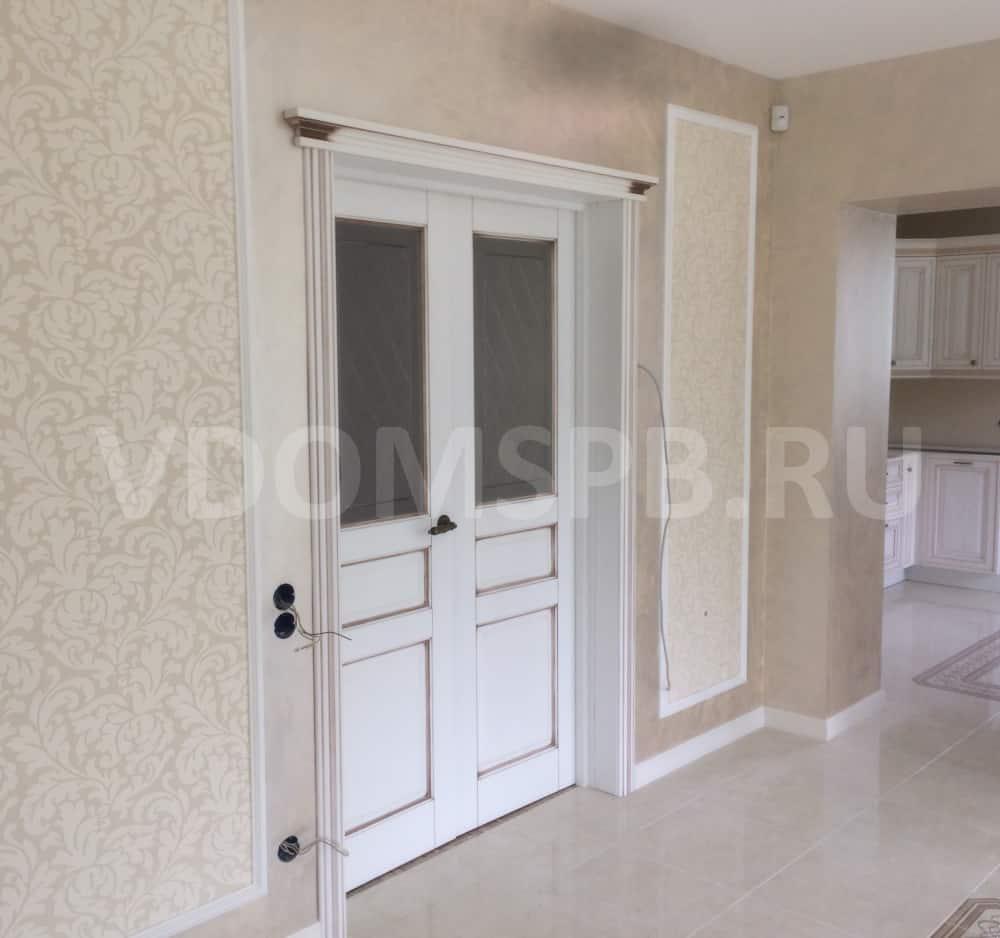 Двустворчатая белая дверь из массива ольхи с патиной в загородном доме
