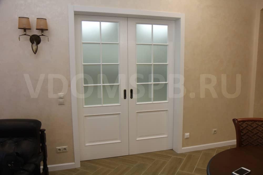 Белые двухстворчатые раздвижные двери между гостинной и кухней