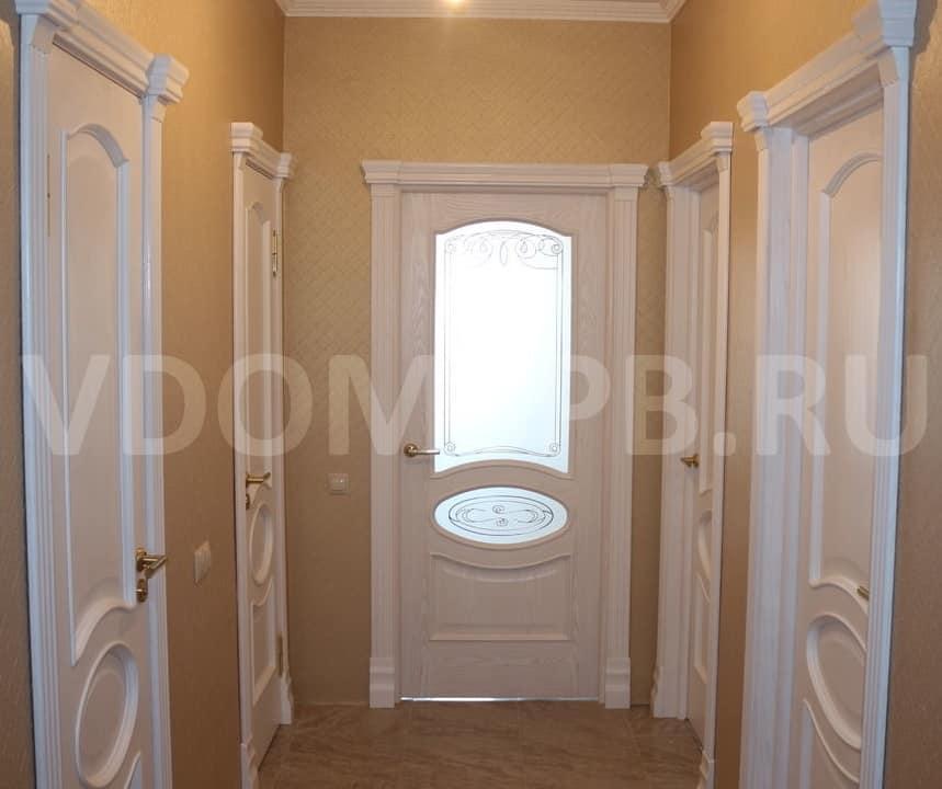 Белые двери с резными наличниками и капителями