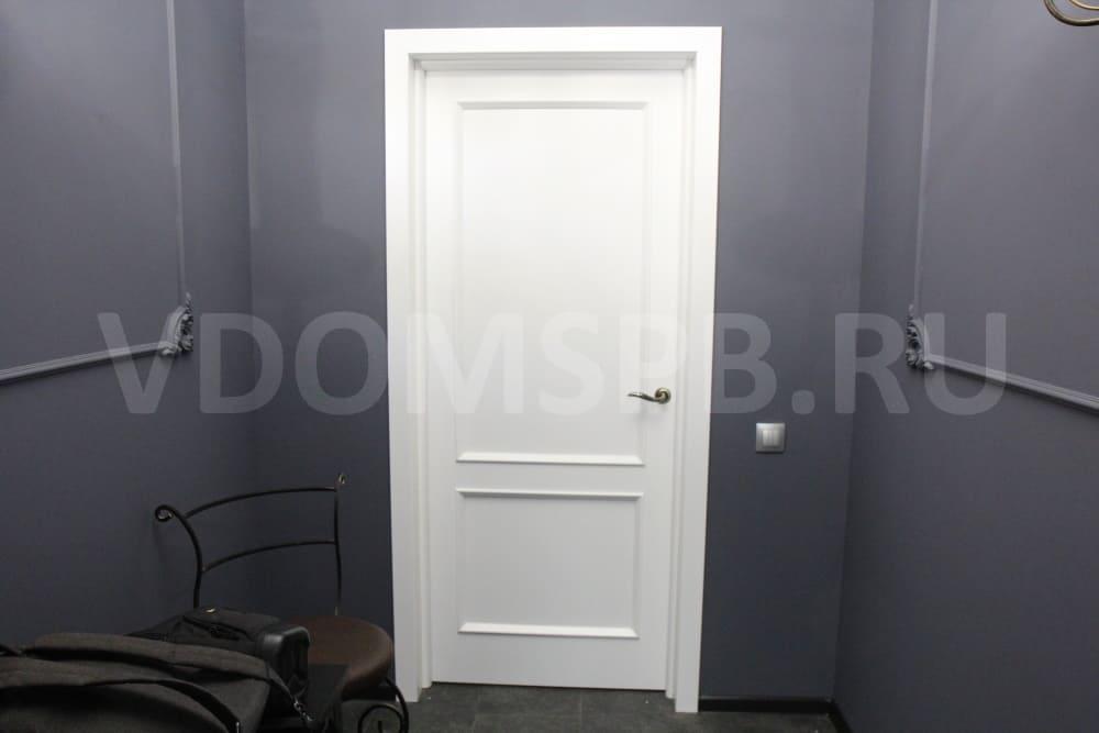 Белая дверь в интерьере с темными стенами и полом
