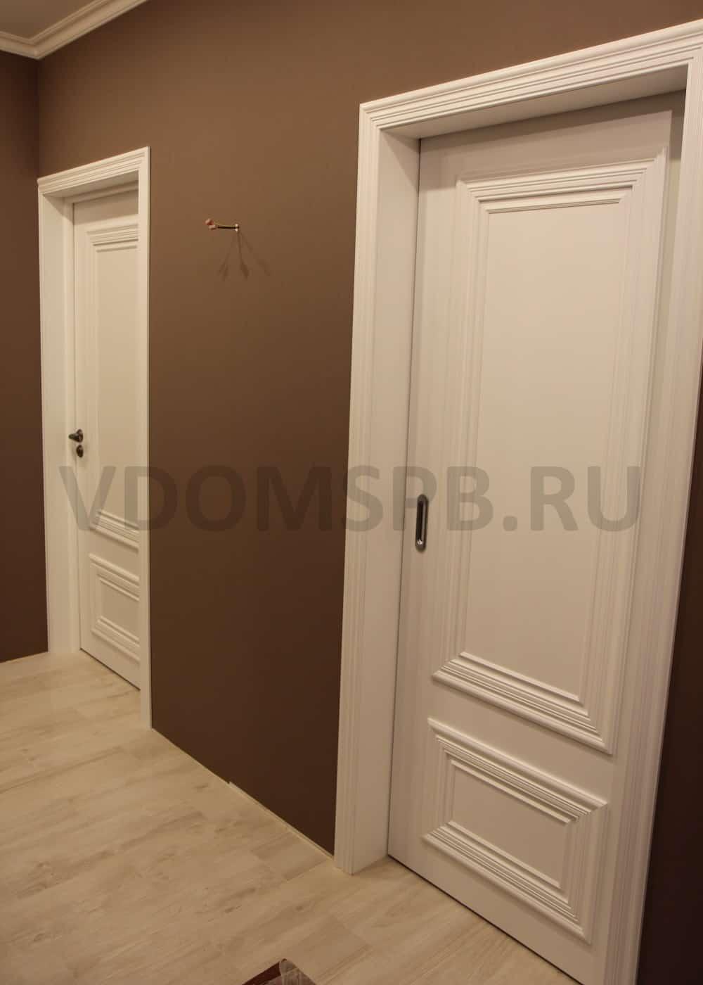 Белая дверь с широким багетом в пенале в стене