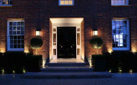 Черная двухстворчатая дверь – главный акцент на кирпичном фасаде