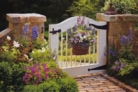 Декоративная корзинка с цветами подчеркнет деревенский стиль оформления садовой калитки