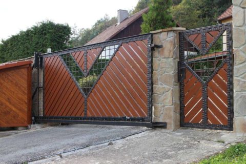Массивная конструкция откатных ворот сочетается с каменным ограждением
