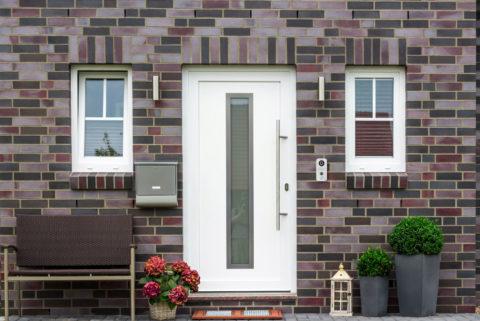 На фоне слишком пестрого фасада будет уместна светлая дверь в простом исполнении