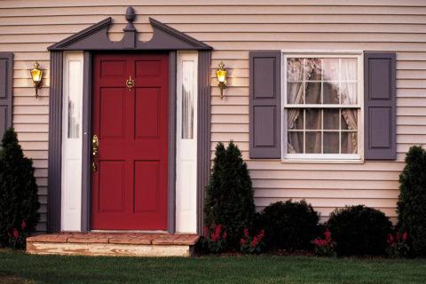 Оригинальная форма обрамления двери подчеркивает ее яркий оттенок и выделяет на лаконичном фасаде