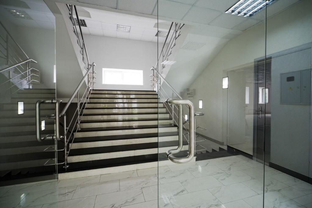 Стеклянная качающаяся дверь в офисном вестибюле