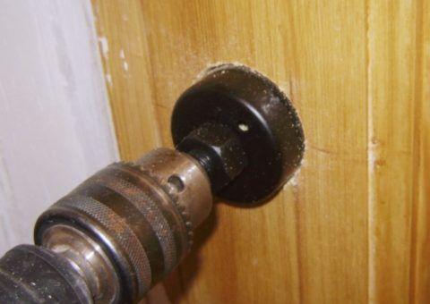 Просверлите с сквозное отверстие в двери коронкой согласно разметке