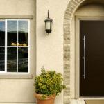 Современный стиль входной двери органично сочетается с арочным проемом крыльца