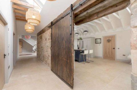 В просторном помещении можно смело использовать массивную конструкцию, поддержанную грубыми деревянными балками