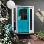 Яркая светлая дверь визуально облегчает темно-серый фасад дома